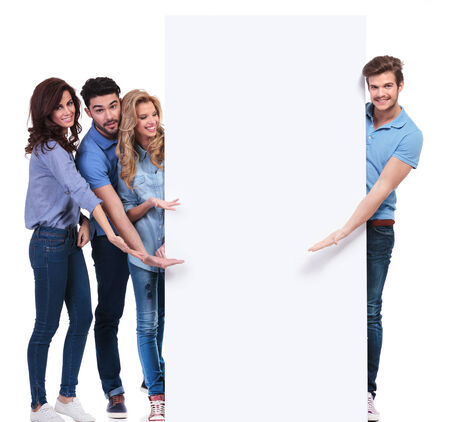 group of casual friends pointing and showing you a blank banner on white background photo