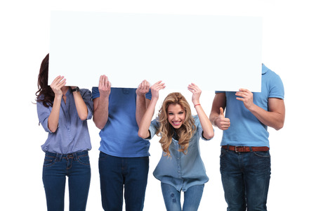 advertisment: casual people hiding behind a blank board, one smiling woman looks to the camera and one man making the ok thumbs up sign