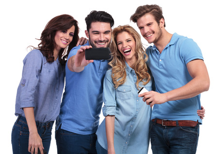smiling man taking a photo of his friends with his smart phone on white background Stock Photo