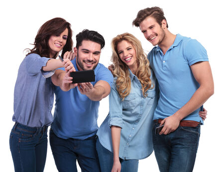two couples of young people taking their picture with a phone on white background photo