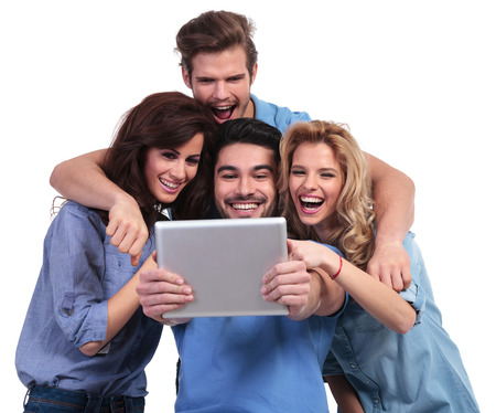 excited group of friends reading surprising stuff on their tablet pad computer on white background photo