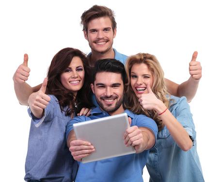 personas leyendo: Grupo ocasional de la gente que lee buenas noticias en su ordenador de la pista de la tableta y hacer las ok signo de los pulgares sobre fondo blanco
