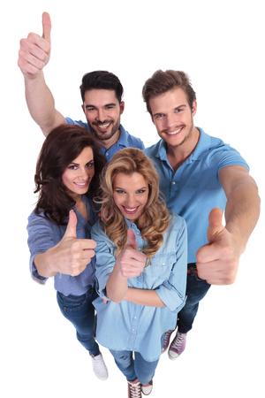 imagen de gran angular de un grupo de gente ocasional que sonríe y que hacen las ok pulgares en señal de mano en el fondo blanco Foto de archivo