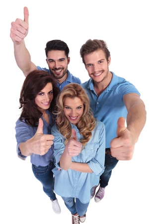 wide angle picture of group of casual people smiling and making the ok thumbs up hand sign  on white background photo