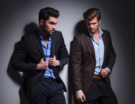 modelos hombres: dos modelos masculinos calientes que presentan contra el fondo del estudio, uno mirando a otro lado y uno tirando cuello de su traje Foto de archivo