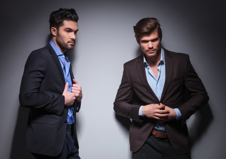 two male fashion models posing in studio, one with shoulder against the wall looking away