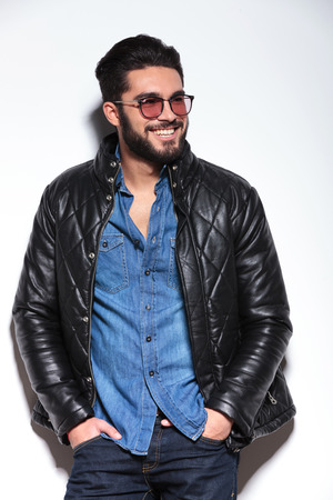 happy smiling casual man in leather jacket looking away to his side photo