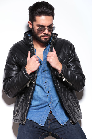 sad man in leather jacket and sunglasses looking down in studio photo
