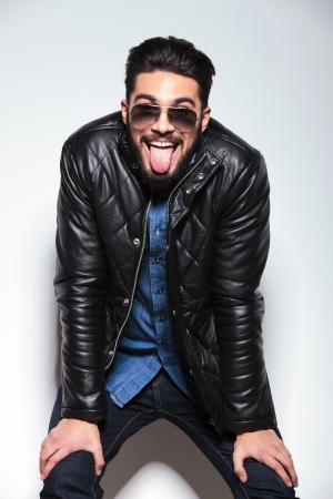 happy fashion man in leather jacket sticking out his tongue and smiles photo