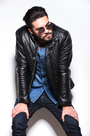 young man in leather jacket and sunlasses looking to his side while resting against studio wall photo