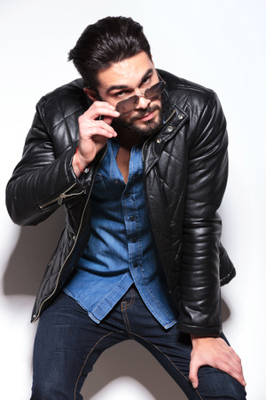 young man in leather jacket taking off his sunglasses and leaning against studio wall photo