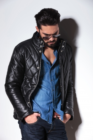 angry fashion man in leather jacket and sunlasses posing against studio wall photo