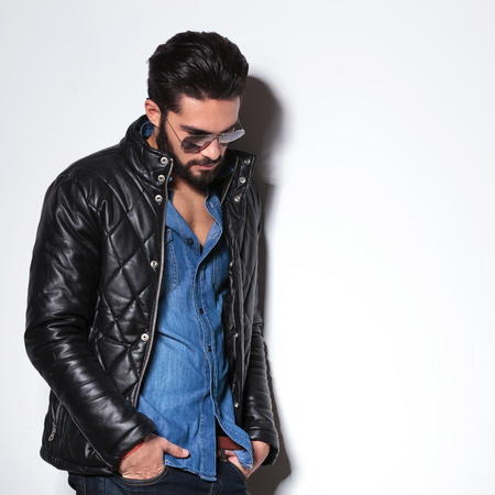 side view of a fashion man in leather jacket looking down in studio photo