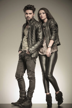 fashion couple in casual leather jackets posing in studio, full body picture photo