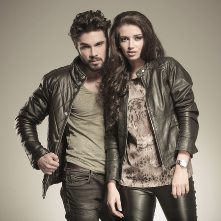 young couple posing in studio, dressed in leather jackets photo