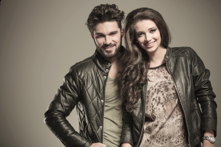 happy fashion couple in leather jackets smiling to the camera in studio photo