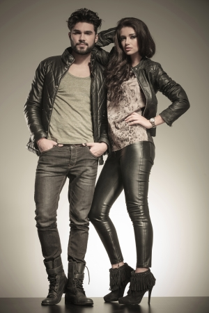 in love couple dressed in leather clothes in a fashion pose in studio photo