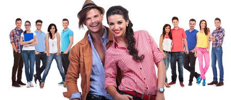 young couple laughing in front of a large group of casual friends on white background photo