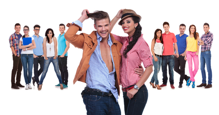 happy young couple in front of a large team of casual people on white background photo