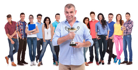 old casual man holding a trophy cup in front of his winning young team of people on white background photo