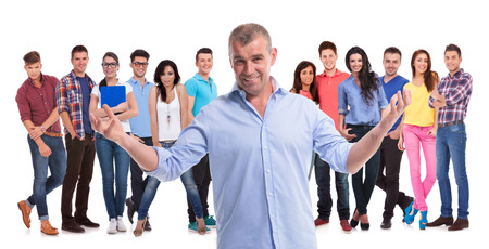 mature casual man welcoming to his young team of casual people on white background photo