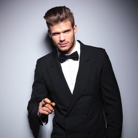 happy elegant fashion man in tuxedo smiling while smoking a cigar photo