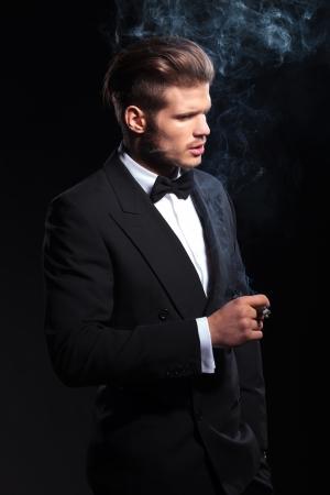 neck ties: side of a fashion man in tuxedo smoking a cigar on dark studio background