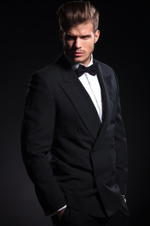 view of an elegant office: side view of a fashion man in tuxedo looking away from the camera