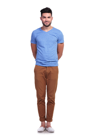back straight: young casual man standing straight with hands at his back on white background