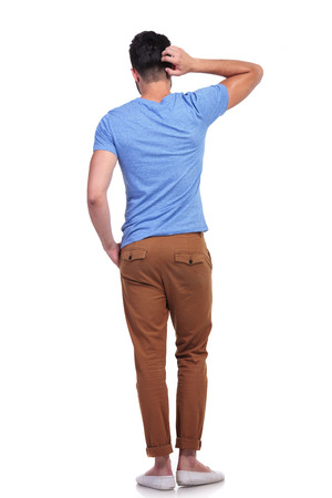 back pocket: back view of a young confused casual man scratching his head on white background
