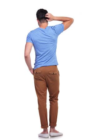 persona confundida: Vista trasera de un joven casual confundido rascarse la cabeza en el fondo blanco
