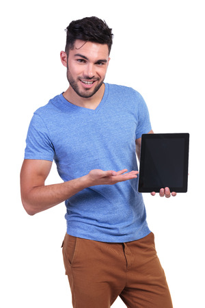 young casual man presenting a talbet pad screen on white background photo