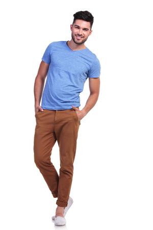cuerpo entero: foto de cuerpo entero de un joven casual de pie con las manos en los bolsillos y sonrisas Foto de archivo