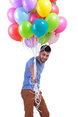 feliz casual hombre regalando un montón de globos en el fondo blanco