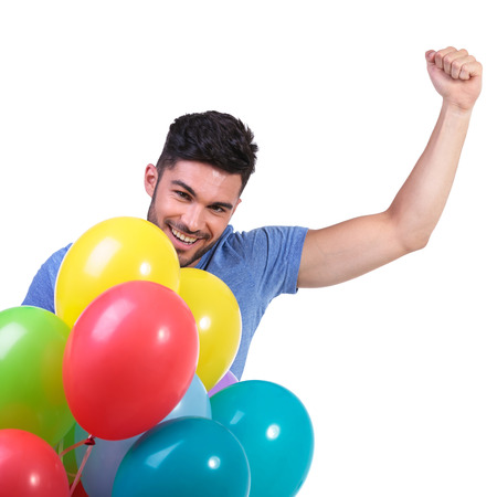 happy winner of a bunch of baloons celebrating with hand inthe air photo