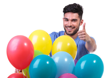 baloons: happy man behind a baloons bunch is making the ok thumbs up sign on white background Stock Photo