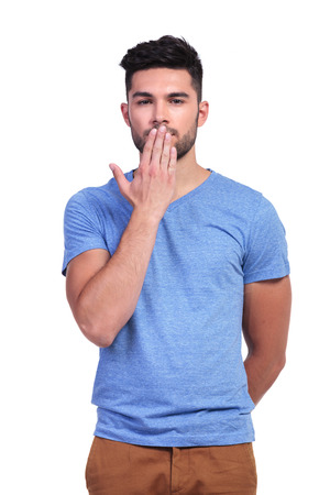 hand on mouth: casual young man covering his mouth with his hand on white background