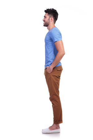 side view of a young casual man standing in line on white background