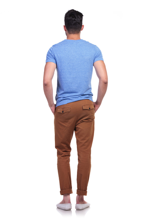 back view of a young casual man standing in line with hands in pockets photo