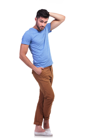 relaxed young casual man standing with hand on head, full body picture