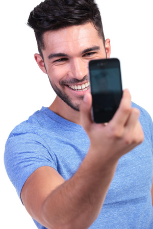 smiling young man taking his own picture with his smart phone on white background photo