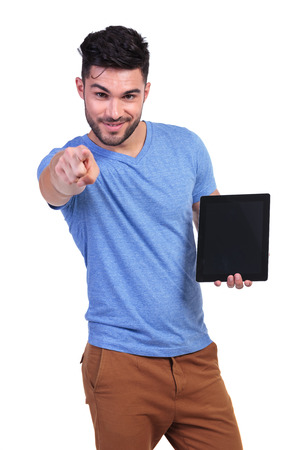 young man presenting a talbet pad and pointing his finger to the camera photo