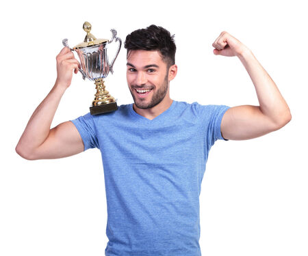 young man flexing his muscle and holding a trophy cup on shoulder photo