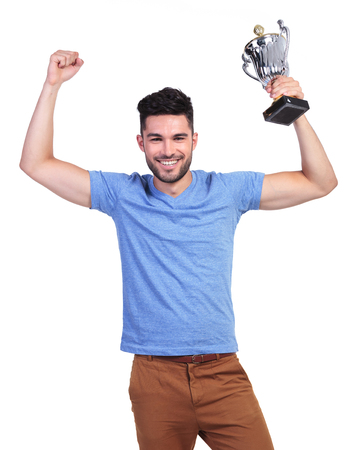 winning young casual man with a big trophy cup and hands in the air photo
