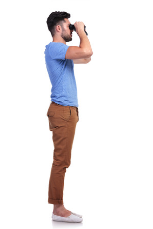 far away look: side view of a casual man looking away through his binoculars on white background