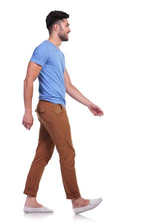 vista lateral de um homem ocasional andar para a frente e sorrindo no fundo branco