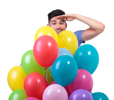 baloons: smiling young man is looking far from behind a baloons bunch