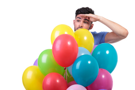 baloons: casual man behind a bunch of baloons is looking away to his side on white background
