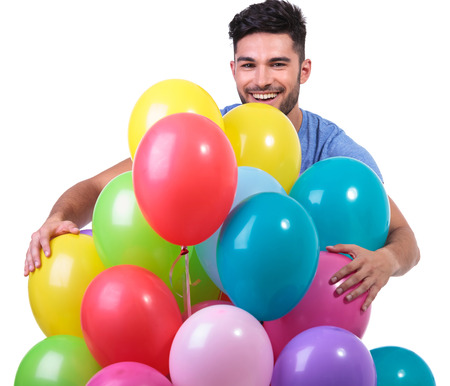 sexy guy: happy casual man embracing a bunch of baloons on white background