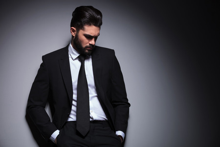 leaning against: front portrait of a young bearded fashion man standing against a wall with his hands in his pockets and  looking down, away from the camera. on a dark background